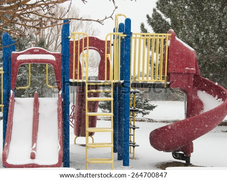 Play set in winter, snow falling and no children to play, slide, monkey bars and ladder - stock photo