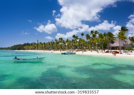 Playa Ba¡varo, Dominican Republic- April 19, 2015: Diving boats moored at the beach with palm trees in the high noon - stock photo