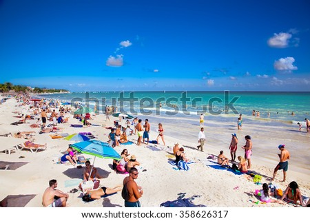 PLAYA DEL CARMEN,MEXICO-NOV 29, 2015: Unidentified tourists on the beach of Playacar at Caribbean Sea in Mexico, Nov 29, 2015. This resort area is popular destination with the most beautiful beaches. - stock photo