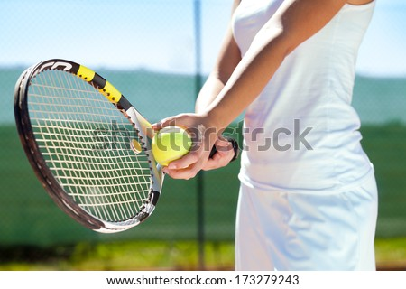 Player's hand with tennis ball and racket - stock photo