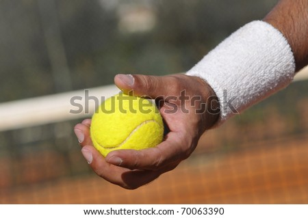 Player's hand with tennis ball in closeup - stock photo