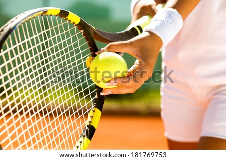Player's hand with tennis ball preparing to serve - stock photo