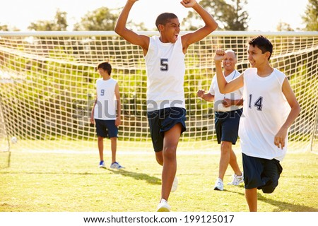 Player Scoring Goal In High School Soccer Match - stock photo