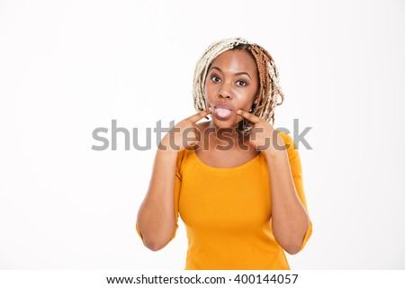 Playful amusing african american young woman showing tongue over white background - stock photo
