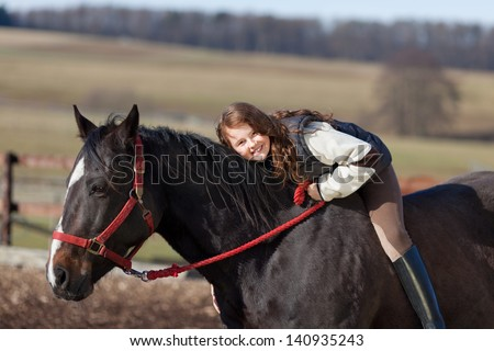 Playful and confident young girl riding on the back of a dark bay horse - stock photo
