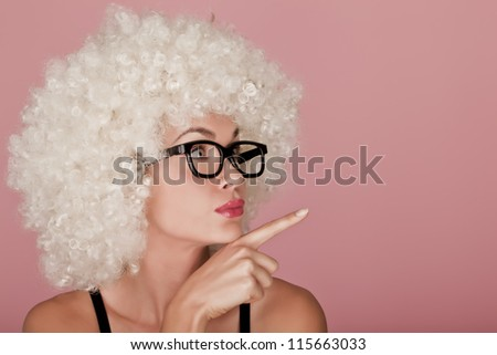 Playful and funny woman wearing a curly wig on a pink background. Funny face. - stock photo