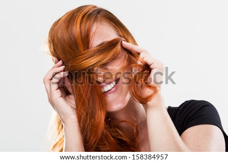 Playful and happy young redhead woman smiling and being shy covering her eyes with the hair - stock photo