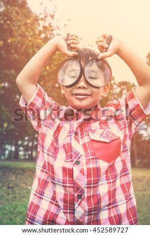 Playful asian child enjoying at park on vacation. Young smart boy peers at camera through two magnifying glass on blurred nature background. Outdoors in the day time with bright sunlight. Warm tone. - stock photo