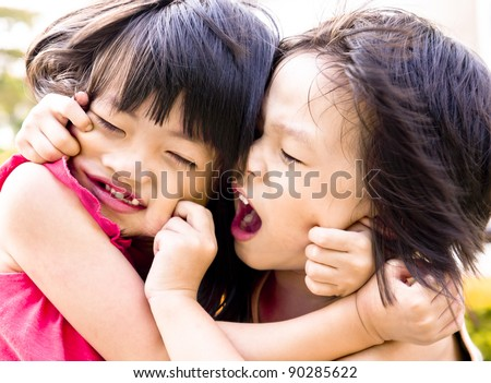 Playful Asian siblings pulling each other faces. - stock photo