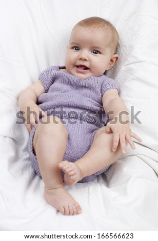 playful baby lying down on white sheet - stock photo