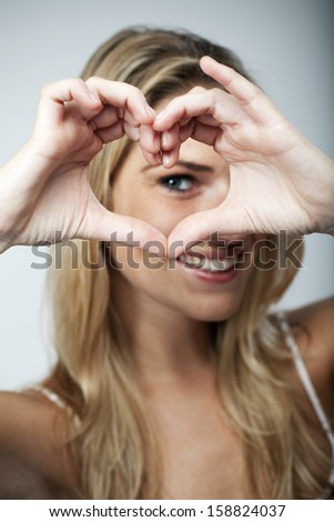Playful beautiful young blond woman making a heart gesture with her fingers to show her love and affection or that she likes something - stock photo
