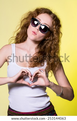 Playful beautiful young woman with sunglasses making a heart gesture with her fingers to show her love and affection or that she likes something. Reflected in sunglasses with heart-shaped - stock photo