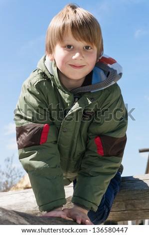 Playful blond boy climbing at outdoor playground - stock photo