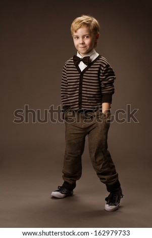 Playful boy in vintage style, kids fashion over brown background - stock photo
