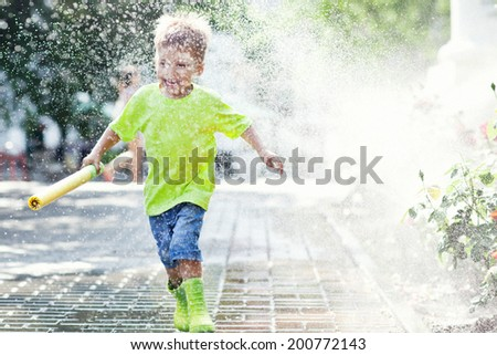 Playful boy runing on rainy summer day  - stock photo