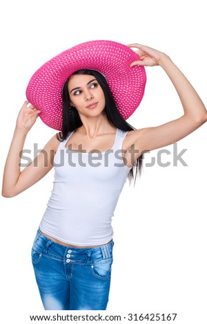 Playful casual girl in bright pink summer straw hat looking away out of frame holding brims, over white background - stock photo