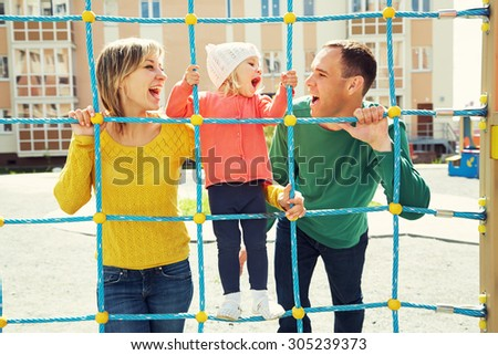 playful child with parents at the playground outdoor. Mom, dad and child - stock photo