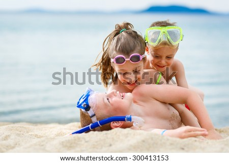 Playful children on the beach with scuba gear - stock photo