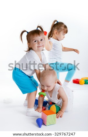 Playful children playing with toys on white background. The little girl is helping another to stand up from the floor. - stock photo