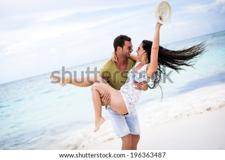 Playful couple at the beach sharing a fun moment - stock photo