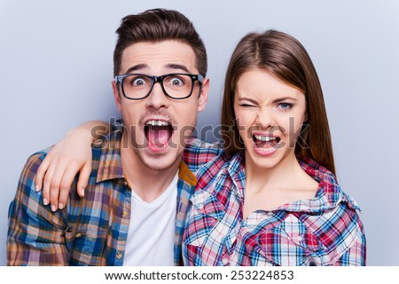 Playful couple. Beautiful young loving couple making faces at camera while standing against grey background - stock photo