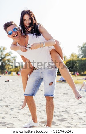 Playful couple enjoying their summer vacation as the man carries the woman piggyback - stock photo