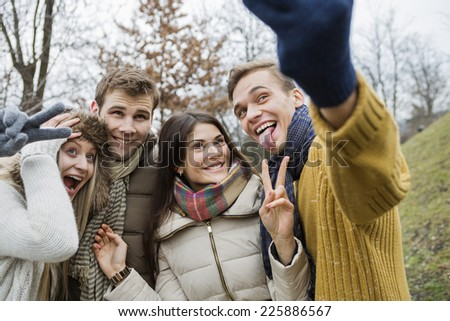 Playful couples gesturing while taking self portrait in park - stock photo