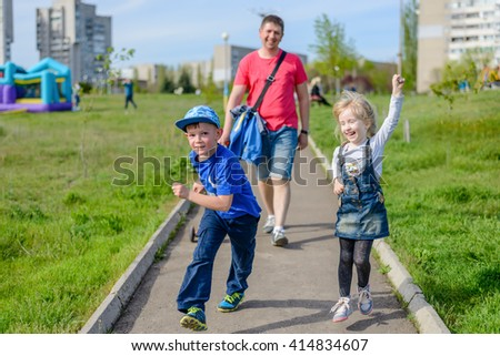 Playful exuberant young children with their father laughing, running and jumping as they walk along a pathway through an urban park - stock photo