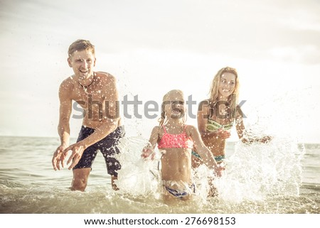 playful family spraying water and having fun. concept about vacation, summer,fun, family and people. - stock photo