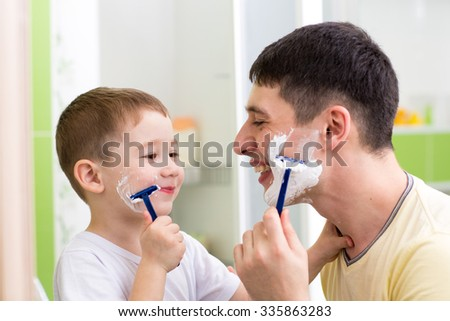 playful father and kid son shaving together at home bathroom - stock photo