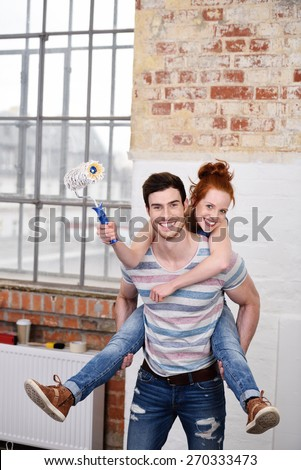 Playful fun loving young couple enjoying a piggy back ride while redecorating their new house - stock photo