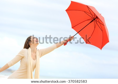 Playful girl joking with a red umbrella on the beach with the sky in the background - stock photo