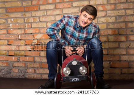 Playful handsome young man having fun riding a vintage toy truck in front of a wall looking at the camera with a happy smile - stock photo