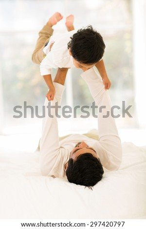 playful indian father lying on the bed and lifting up his little son at home - stock photo