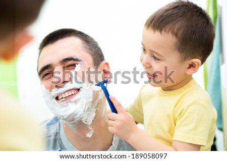 playful kid and dad shaving together at home bathroom - stock photo