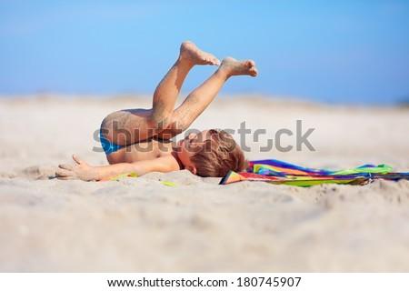playful kid having fun on the beach - stock photo