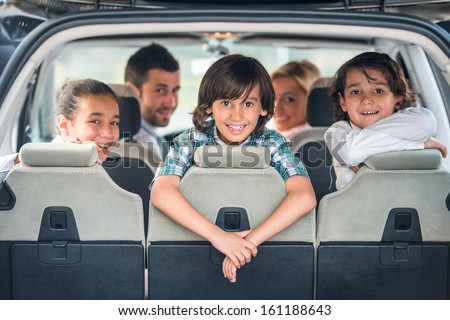 Playful kids posing in the back of a car with their parents in background - stock photo