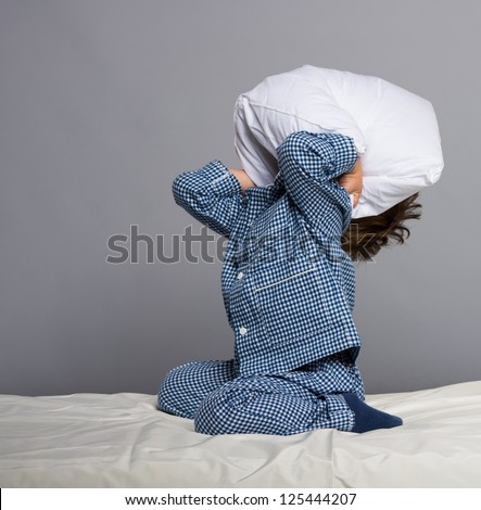Playful little boy wearing blue pyjamas in bed - stock photo