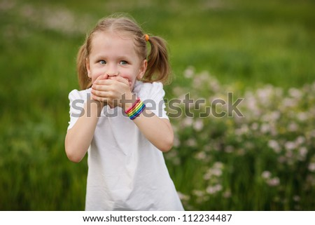 Playful little girl covering her mouth with palms, going to say nothing, outdoors - stock photo