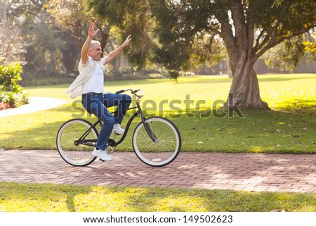 playful middle aged man riding a bike outdoors with arms up - stock photo