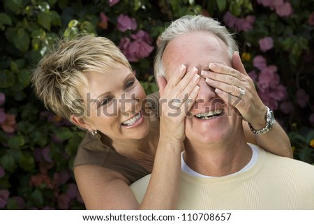 Playful middle aged woman covering eyes of husband - stock photo