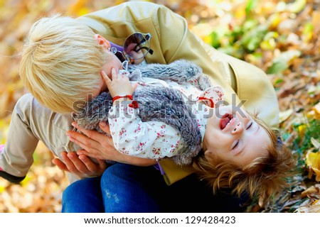 playful mother and baby having fun in autumn park - stock photo