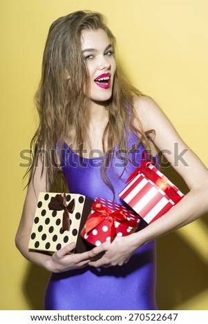 Playful smiling girl in violet jumpsuit holding colorful boxes of presents standing on yellow background, vertical photo - stock photo