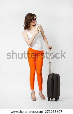 Playful smiling young woman in orange pants with suitcase pointing to the side, full length portrait - stock photo