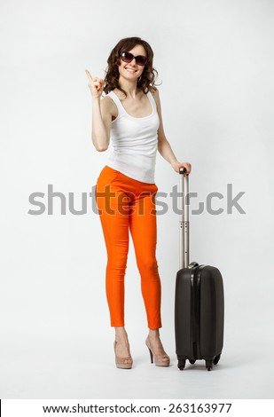 Playful smiling young woman in orange pants with suitcase pointing up, full length portrait - stock photo