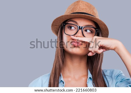 Playful style. Close-up portrait of a young woman holding a finger up to her nose while looking away - stock photo