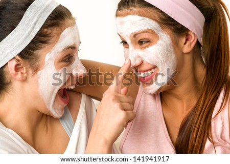 Playful teen wearing mask touches her friend's nose - stock photo
