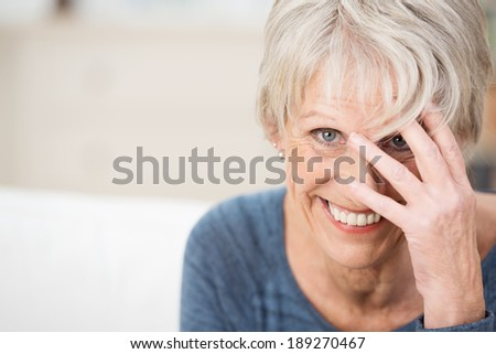 Playful vivacious elderly woman peering through her outspread fingers at the camera with a mischievous smile, with copyspace - stock photo
