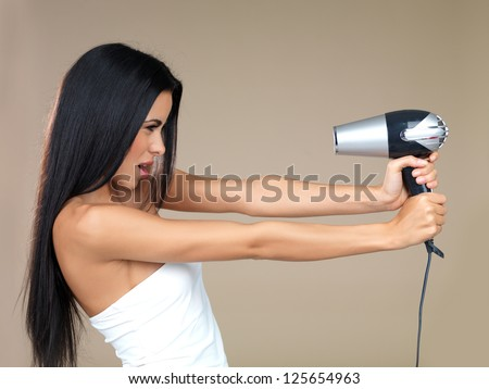 Playful woman having fun with a hairdryer holding it out in her outstretched hands pointing back at her own face isolated on beige - stock photo