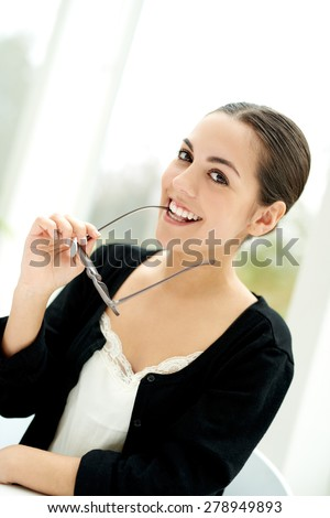 Playful young businesswoman glancing sideways smiling at the camera while holding her eyeglasses in her hand - stock photo